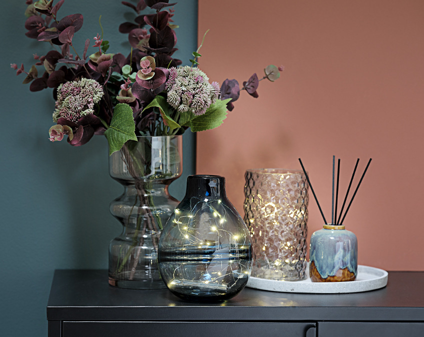 Vases with light strings and flowers on a table