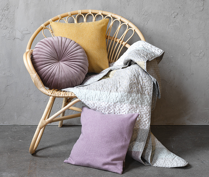 Rattan armchair with cushions and throw