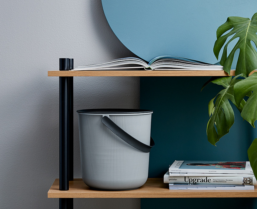 Storage bucket with a lid and a handle on a shelf a bookcase