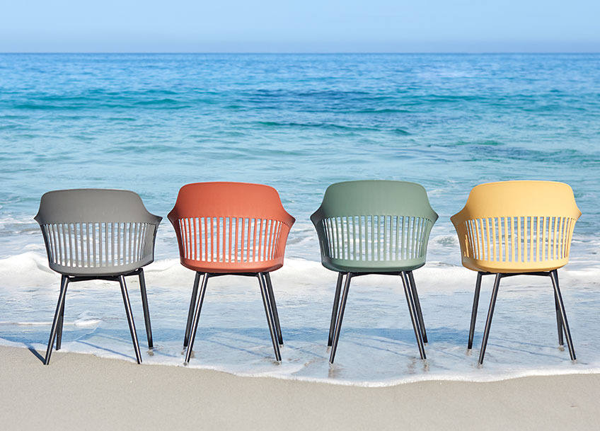 Four garden chairs in different colours on a beach