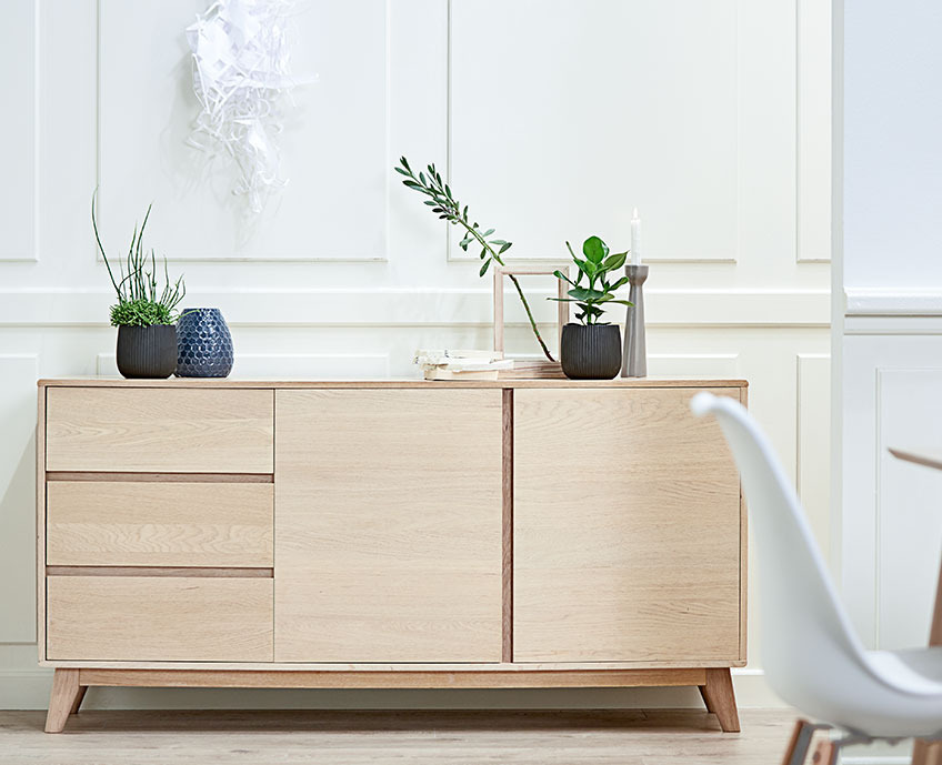Oak sideboard with three drawers and two doors in a dining room