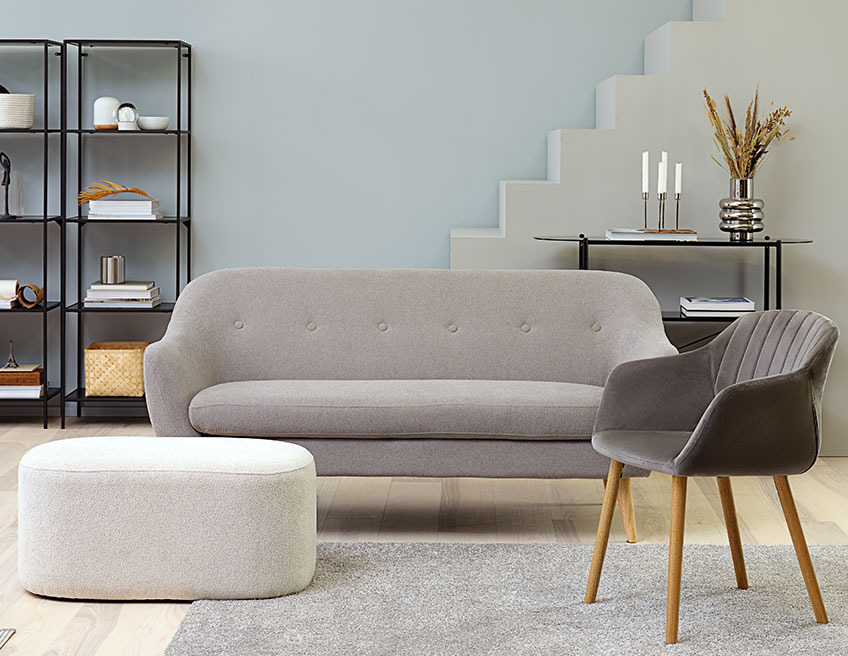 Large, oval footstool in a living room with a sofa and a dining chair