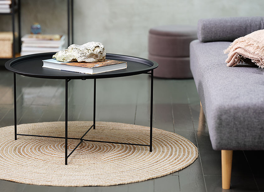 A coffee table on a circular rug in front of a sofa