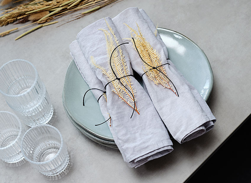 Table set with plate, glasses and cloth napkins decorated with dried leaves and a ribbon