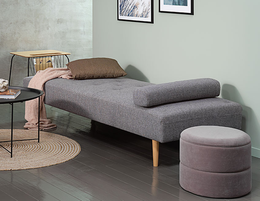 Storage pouffe beside a grey daybed with a cushion and a throw