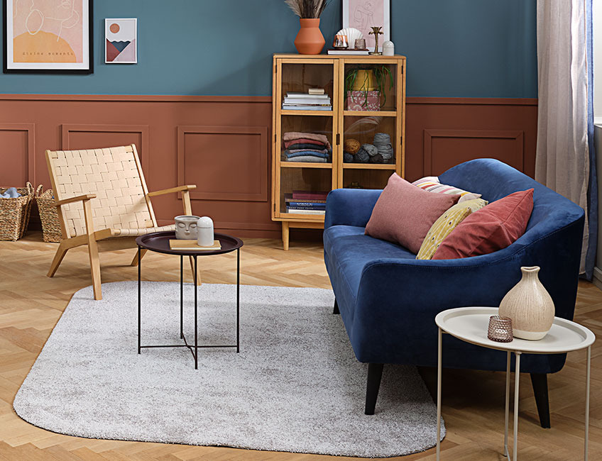 Living room with a light grey rug, an armchair and a sofa with colourful cushions