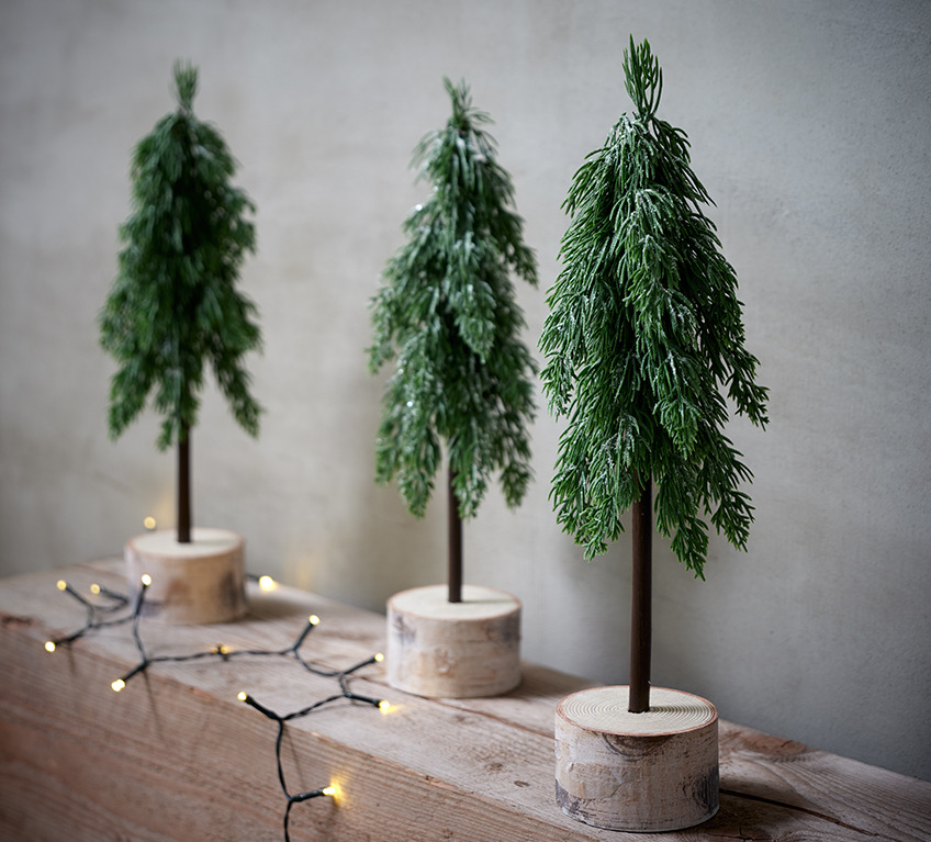 Three artificial pine trees on a log represent modern Christmas décor