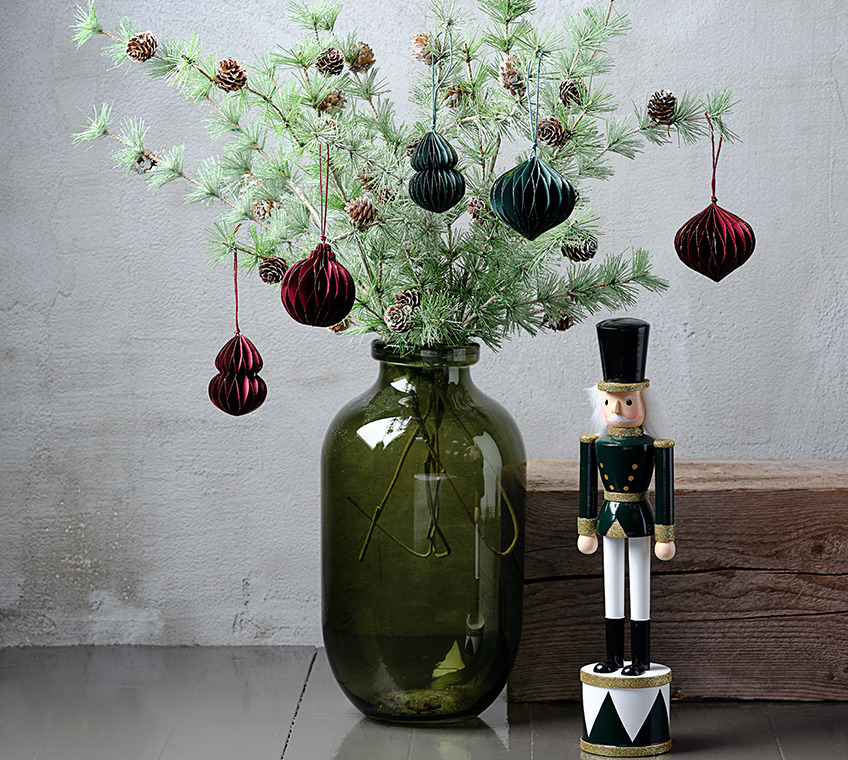 Green glass vase filled with artificial twigs with pinecones, decorated with Christmas ornaments in green and red. Beside it a Christmas figurine