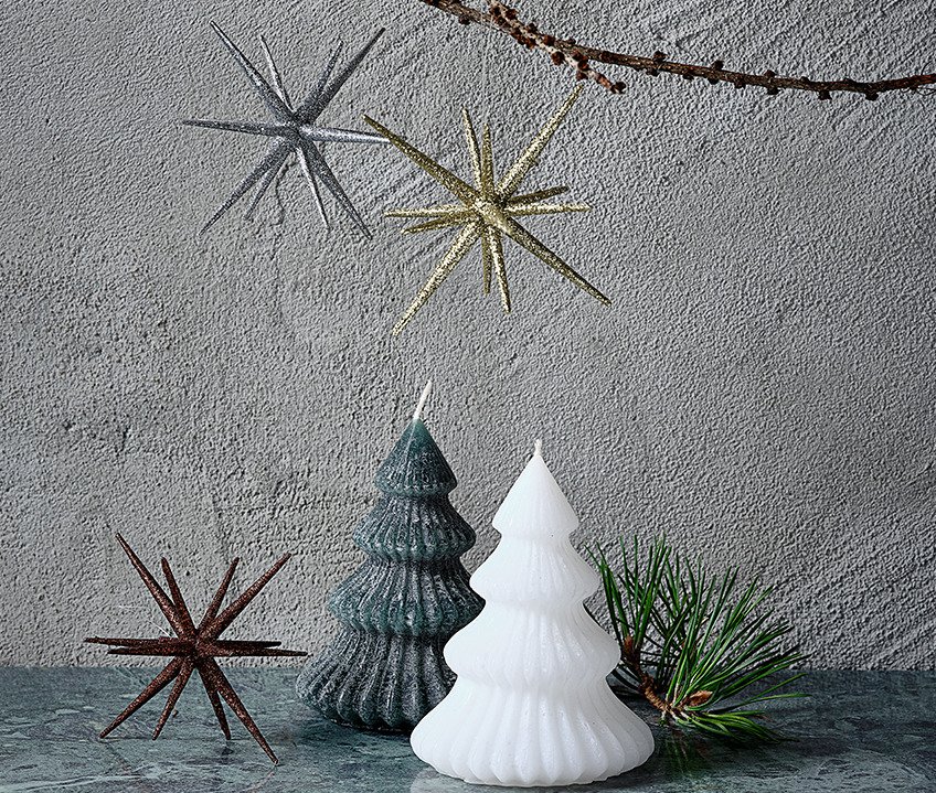 Two candles shaped like Christmas trees and Christmas stars in gold, silver and brown.
