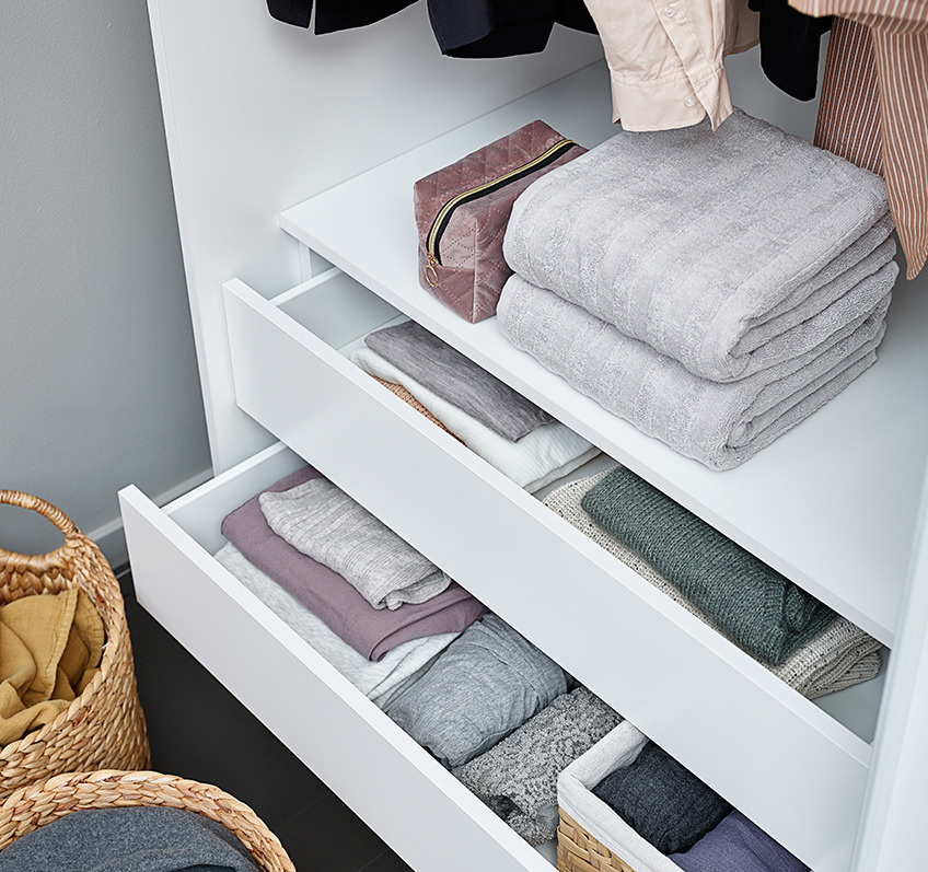 Wardrobe interiors with drawers, towels and clothes