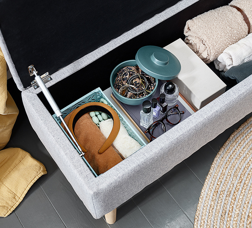 End of bed storage bench with a storage jar, a throw and other items