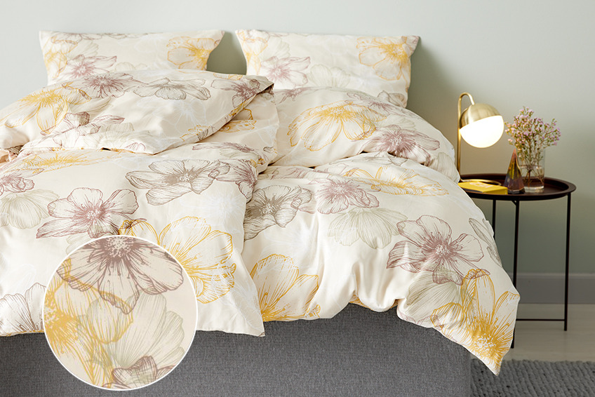 Bed with flowery bed linen in a bedroom with bedside table and table lamp