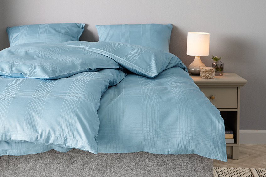Bed with petrol coloured bedding in recycled polyester and cotton