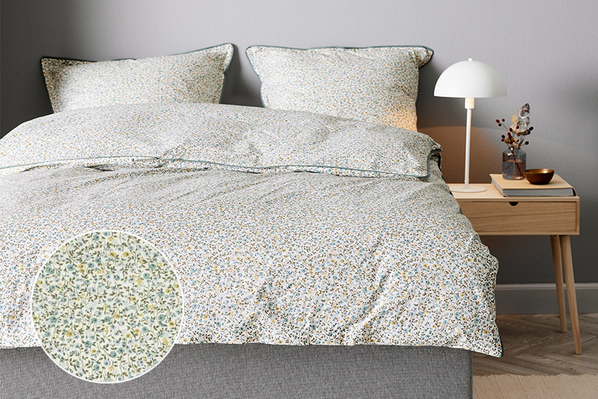 Bed with a flowery duvet cover set in a bedroom with bedside table and white table lamp
