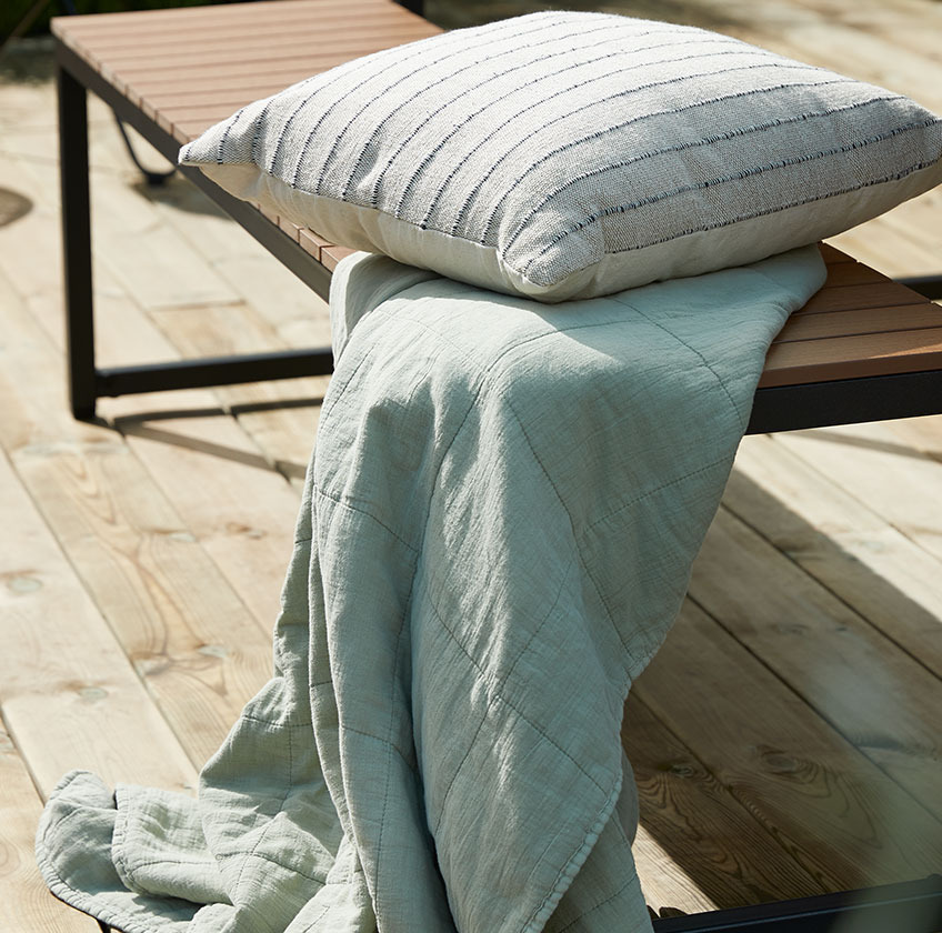 Wood garden bench with a throw and a cushion