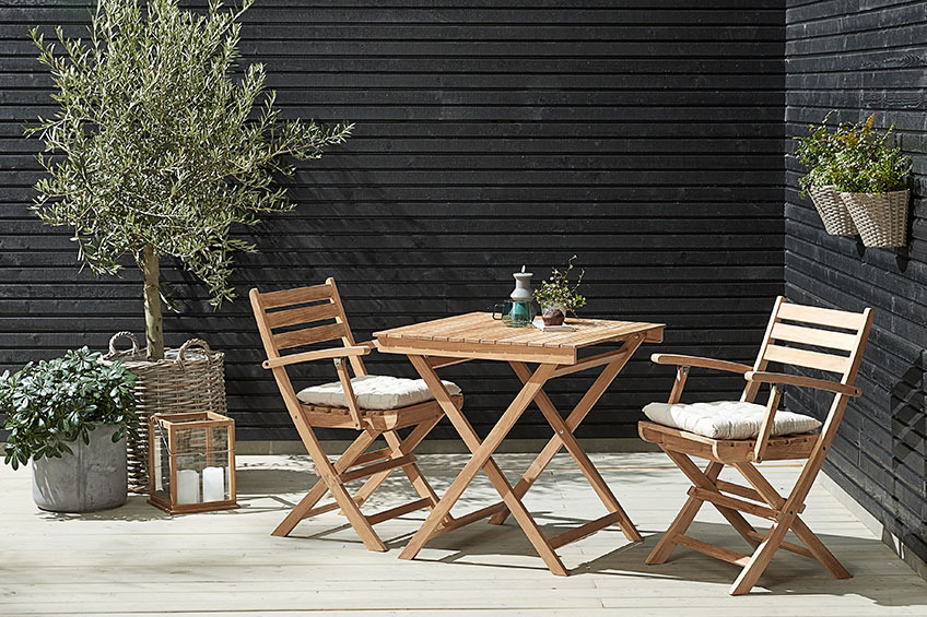 A bistro set with a small table and two folding chairs in the corner on a patio