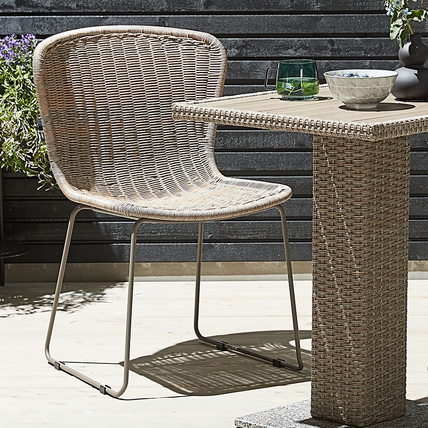 Garden chair with a natural look, made of polyrattan and metal with a bistro table made of polyrattan on a patio