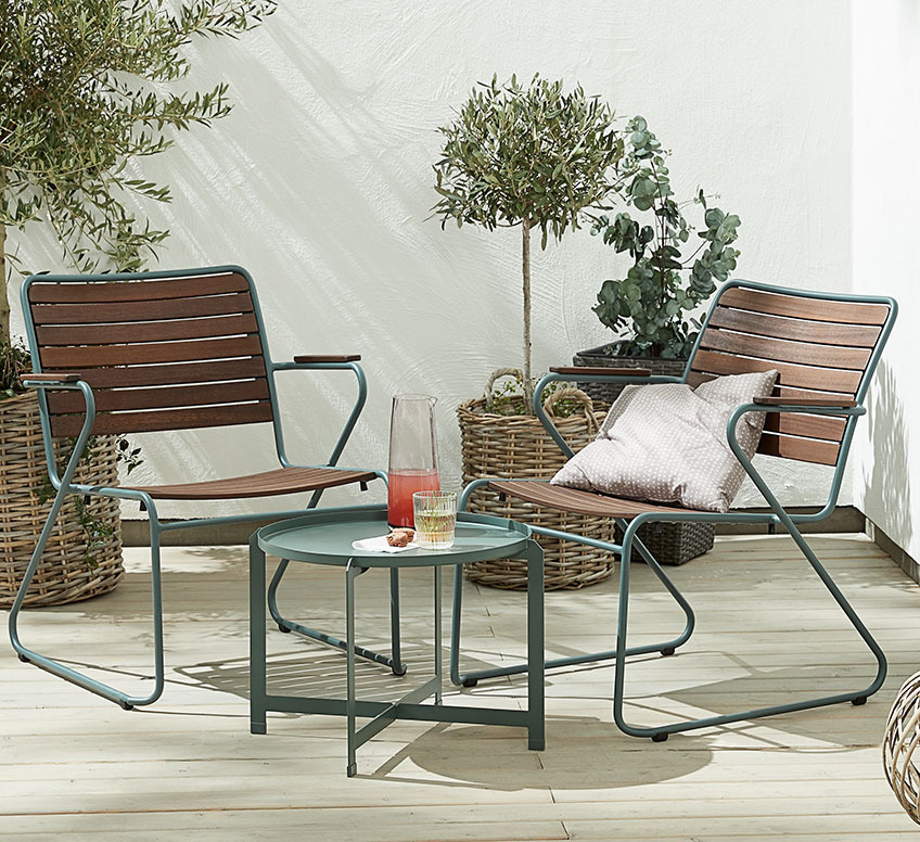 Two wooden garden lounge chairs with green frame and a small green side table on a patio